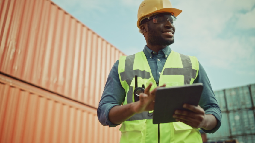 Smiling Portrait of a Handsome African American Black Industrial Engineer in Yellow Hard Hat and Safety Vest Working on Tablet Computer. Inspector or Safety Supervisor in Container Terminal. Royalty-Free Stock Footage #1065943459
