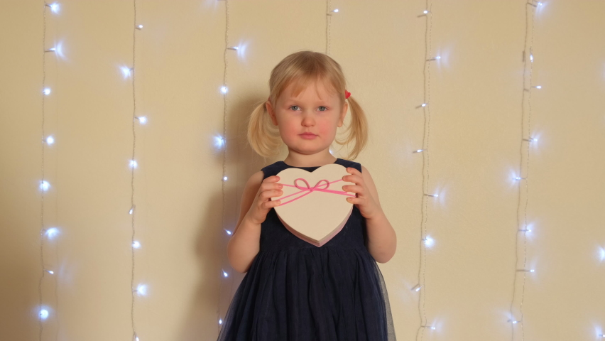 Cheerful Little blonde girl holding a heart-shaped gift box. | Shutterstock HD Video #1065943654
