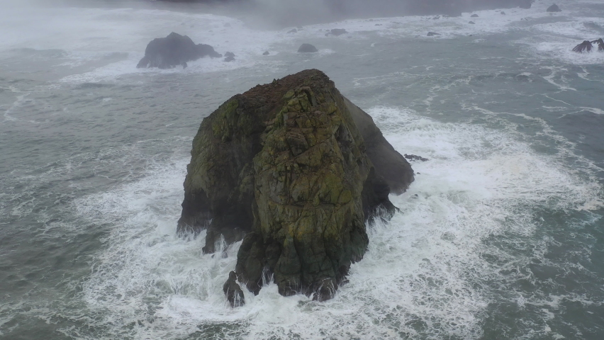 The cold waters of the Pacific Ocean wash against sea stacks and the rocky Northern California coastline in Klamath. The scenic Pacific Coast Highway runs along this amazing part of the west coast. Royalty-Free Stock Footage #1065949945