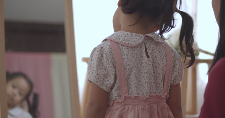 4K Slow motion , Cute Little Asian girl looking in a mirror and her mother was wearing a pink Sweater for a holiday trip. (Happiness family holiday concept) | Shutterstock HD Video #1065950254