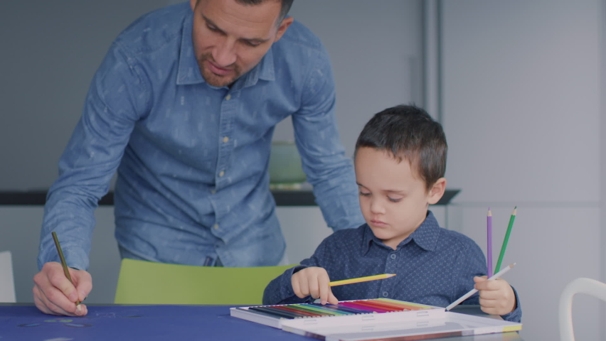 Father drawing meanwhile his son chooses the colours, surrounded by a modern age living room and kitchen. | Shutterstock HD Video #1065951343