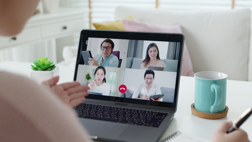 Back view of business woman talking about sale report in video conference. Asian team using laptop and tablet online meeting in video call.Working from home, Working remotely and Social isolation. | Shutterstock HD Video #1065951394