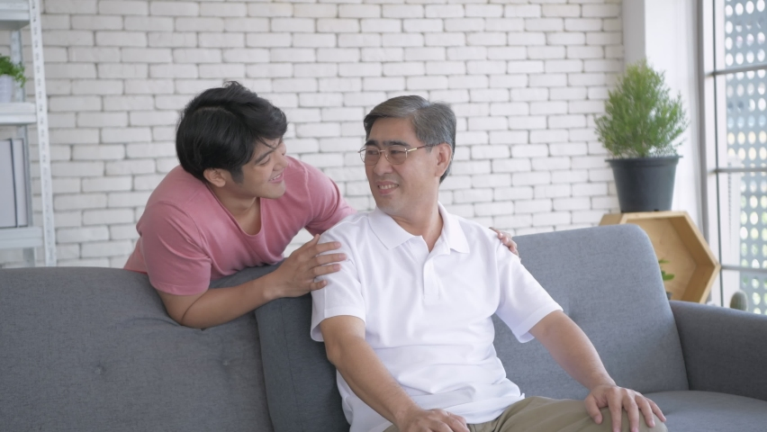 Family concept of 4k Resolution. An Asian son and father are enjoying the living room television. | Shutterstock HD Video #1065951889