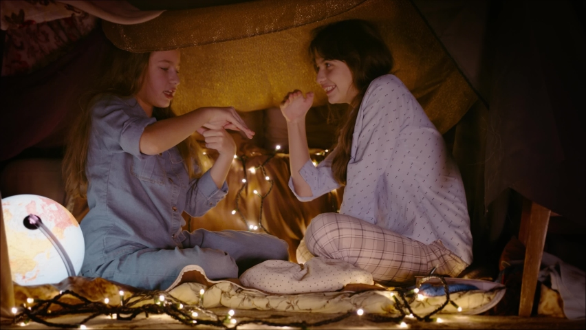 Two little sisters play at home in tent made of blankets and pillows | Shutterstock HD Video #1065952009