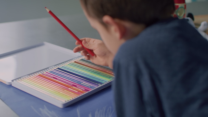Kid choosing colours, meanwhile his father draws beside him. | Shutterstock HD Video #1065952012