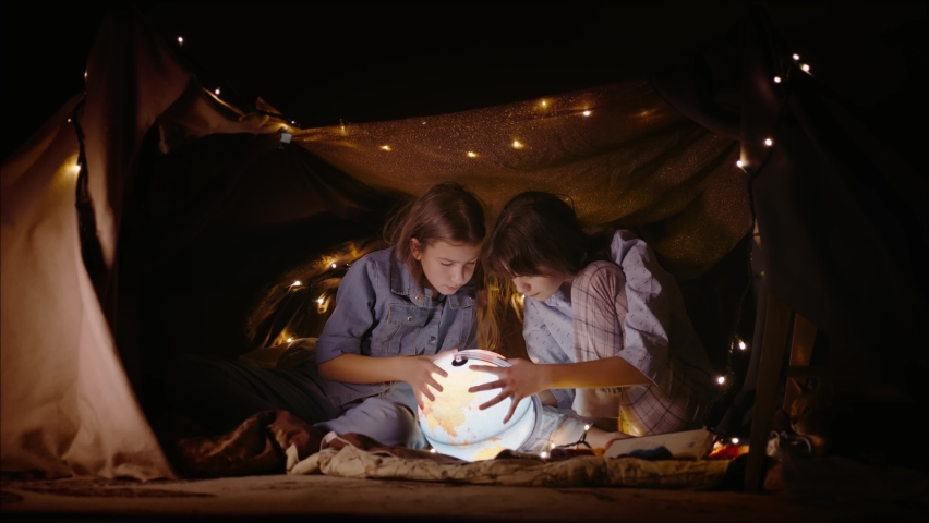 Children examine the globe in a tent made of blankets and pillows. Two curious little girls play together late at night | Shutterstock HD Video #1065952015