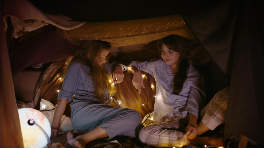 Two little girl friends play together in tent made of blankets and pillows | Shutterstock HD Video #1065952048