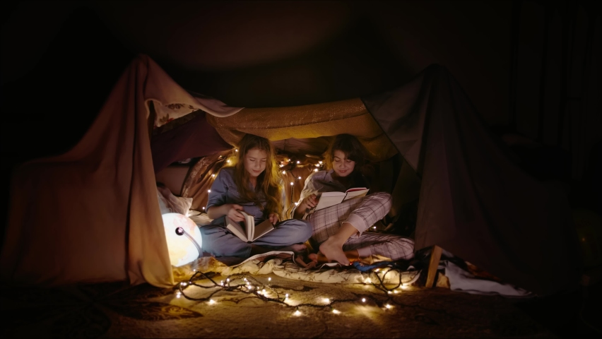 Children built tent at home with blankets and pillows, play there and read books by light of lamps. Two little sister girls made shelter and play in secret place | Shutterstock HD Video #1065952060