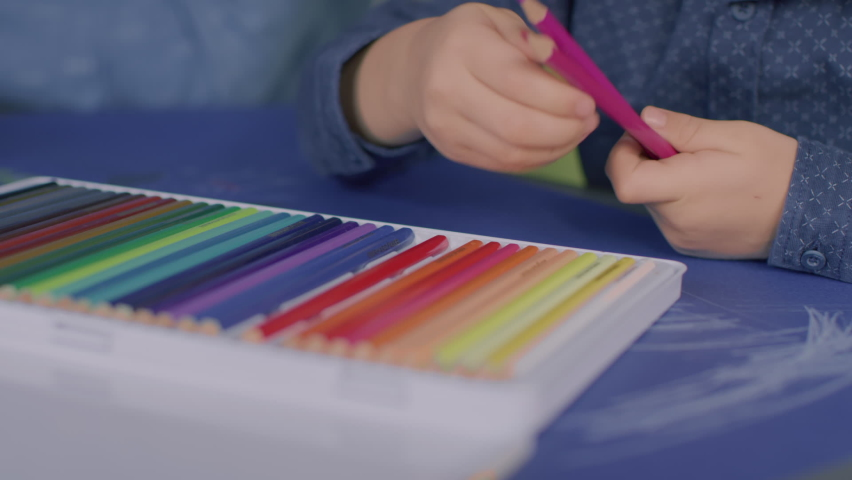 Young kid choosing and arranging colouring pencils. | Shutterstock HD Video #1065952561
