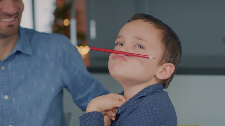Young kid with his dad playing with coloured pencils, making silly faces and colouring. | Shutterstock HD Video #1065952780