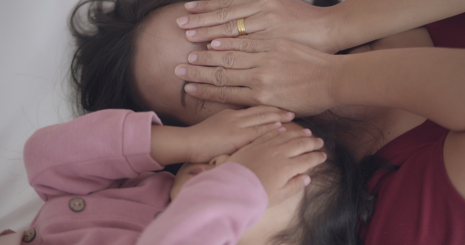 4K slow motion, Asian woman (mom) is lying in bed with her daughter and playing peekaboo, relaxing with family on vacation, happy family holiday  positive relationship concept. | Shutterstock HD Video #1065953641