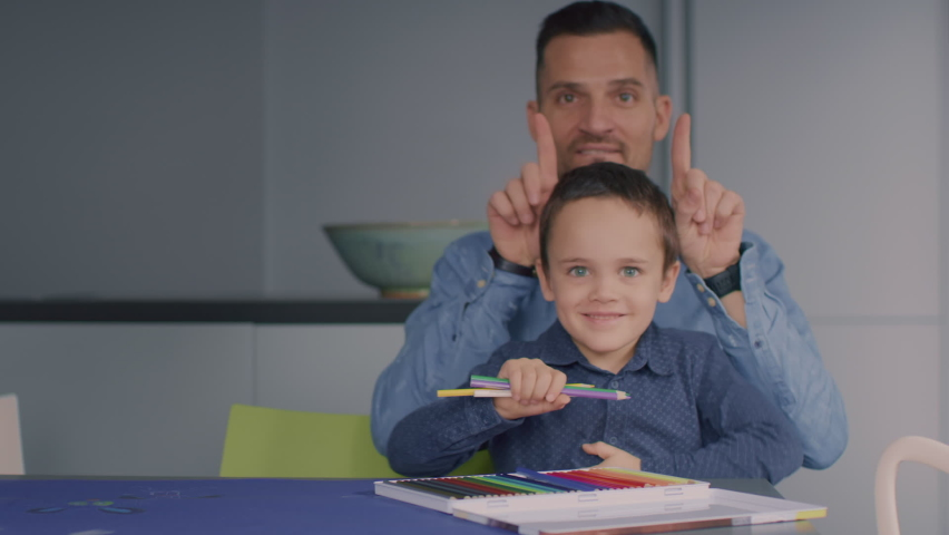 Young kid and his dad holding colouring pencils looking towards the camera, making silly faces and having fun. | Shutterstock HD Video #1065953761