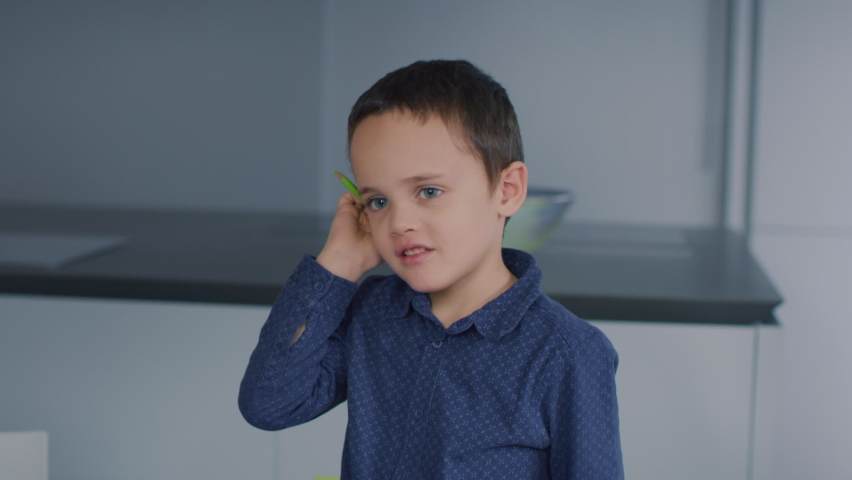 Young happy kid thinking, with a coloured pencil on his ear. | Shutterstock HD Video #1065953824