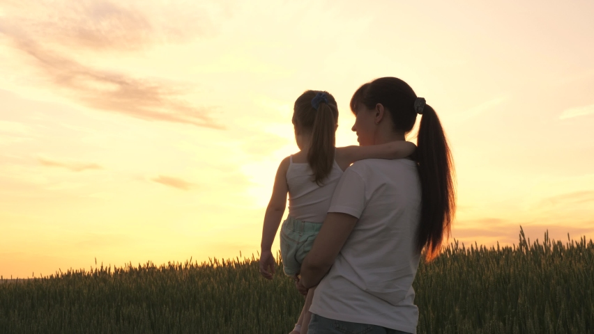 A farmer mom carries a child in her arms through a wheat field. Mom plays with her little daughter at sunset. Mom walks with the baby in the fresh air. Happy family lit by the sun | Shutterstock HD Video #1065953845