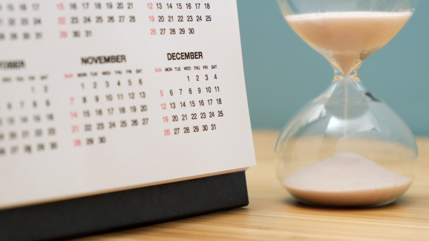 Close up of a calendar and hourglass on wooden table. Concept of starting of new year. Royalty-Free Stock Footage #1065955315