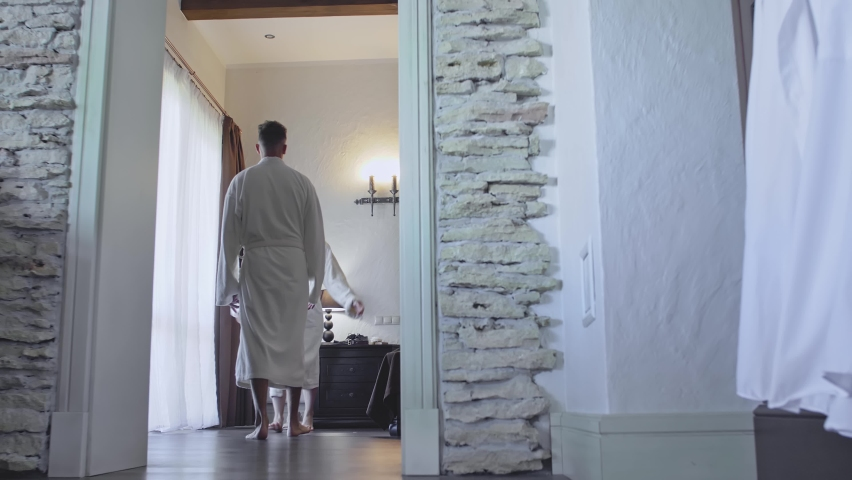 Newlyweds in a hotel room in bathrobes. A young woman in a dressing gown jumps on the man's arms. They hug laugh and spin with happiness.  | Shutterstock HD Video #1065955342