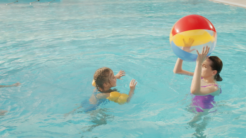 Handheld from-above slowmo shot of happy caucasian family on vacation, swimming in pool and playing with beach ball | Shutterstock HD Video #1065958354