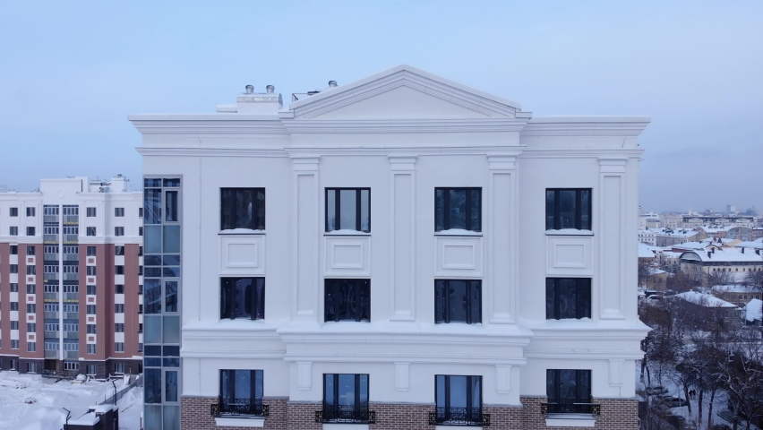 Flying away from a multi-storey building on a drone. Brick building with windows. Modern facade.   Shutterstock HD Video #1065965416