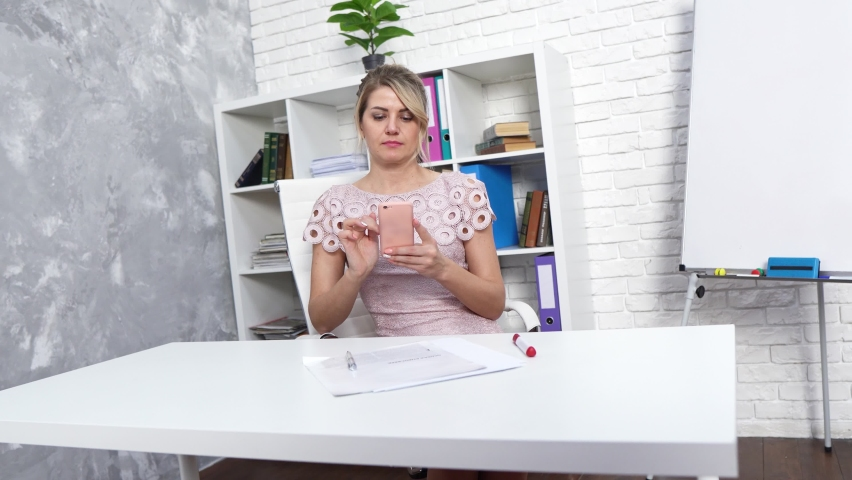 A beautiful girl in a dress works in the office at the table, a girl with a phone, a girl makes a selfie on the phone at the workplace, a girl works with a phone Royalty-Free Stock Footage #1065978904
