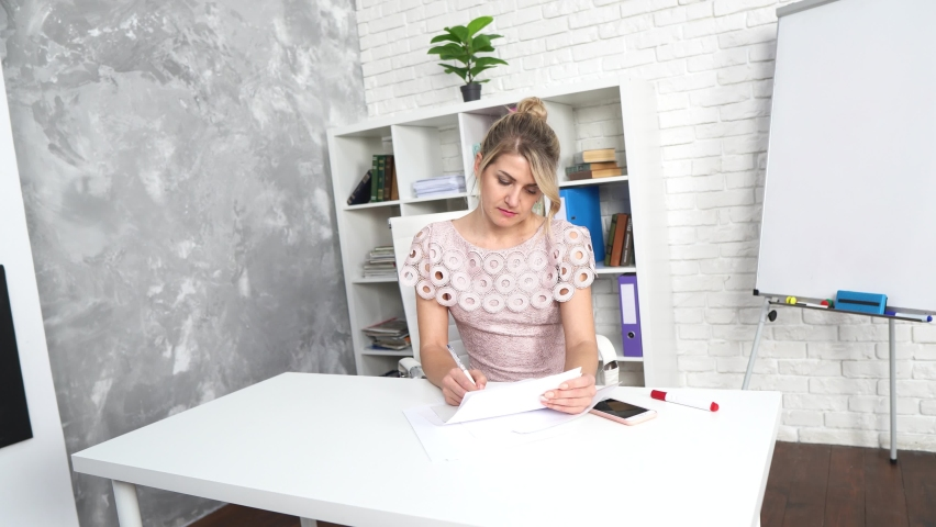 A beautiful girl in a dress works in the office at the table, a blonde at work, a businesswoman, a girl studies Royalty-Free Stock Footage #1065978907
