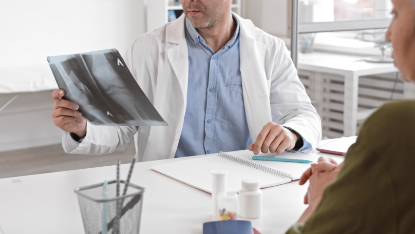 Over-the-shoulder slow motion of unrecognizable patient sitting at medical session across desk from middle-aged Caucasian male therapist checking leg X-rays, taking off glasses and talking | Shutterstock HD Video #1065981721