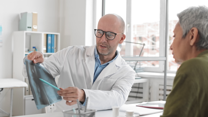 Over-the-shoulder slow motion of middle-aged Caucasian male doctor showing X-rays and talking to cropped senior patient sitting across desk at medical session  | Shutterstock HD Video #1065982408
