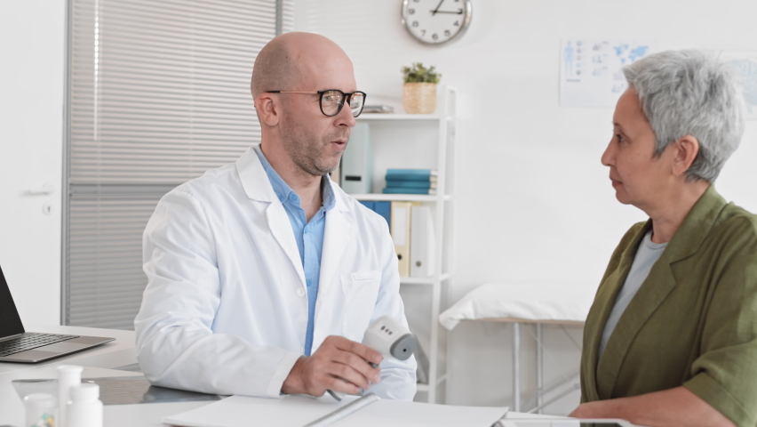Medium of middle-aged male Caucasian therapist talking to and measuring temperature of senior Asian female patient with non-contact infrared thermometer | Shutterstock HD Video #1065982462