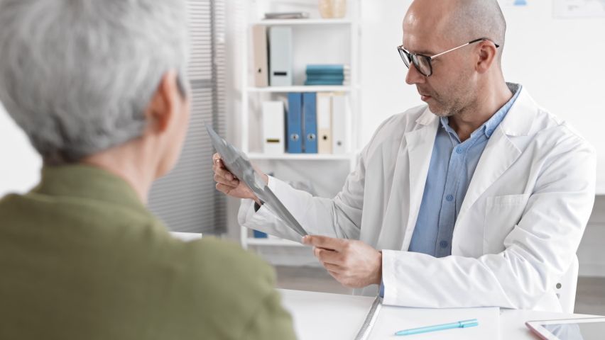 Over-the-shoulder slow mo of unrecognizable patient sitting at medical appointment across desk from middle-aged Caucasian male doctor holding X-rays, taking off glasses and talking | Shutterstock HD Video #1065982654