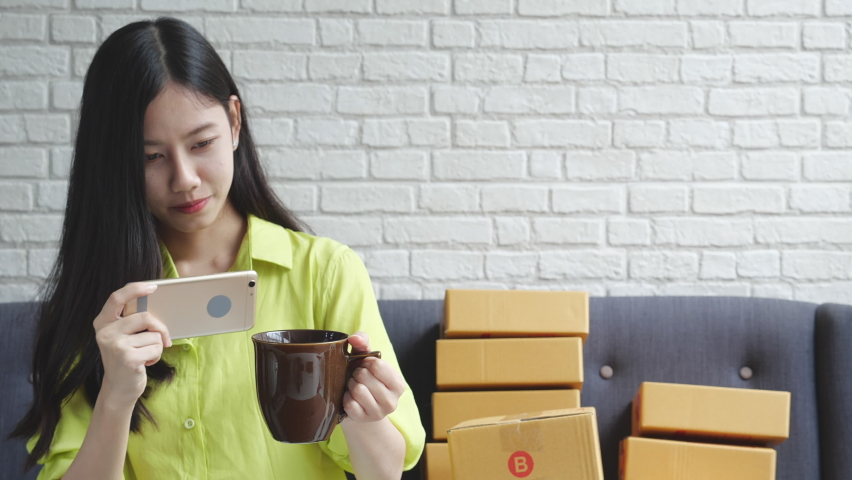 Young asian woman talking a photo to glass with smartphone to sell online at home, business startup or SME, online shopping, e-commerce, entrepreneur merchant sell product, delivery and shipping. | Shutterstock HD Video #1065982681