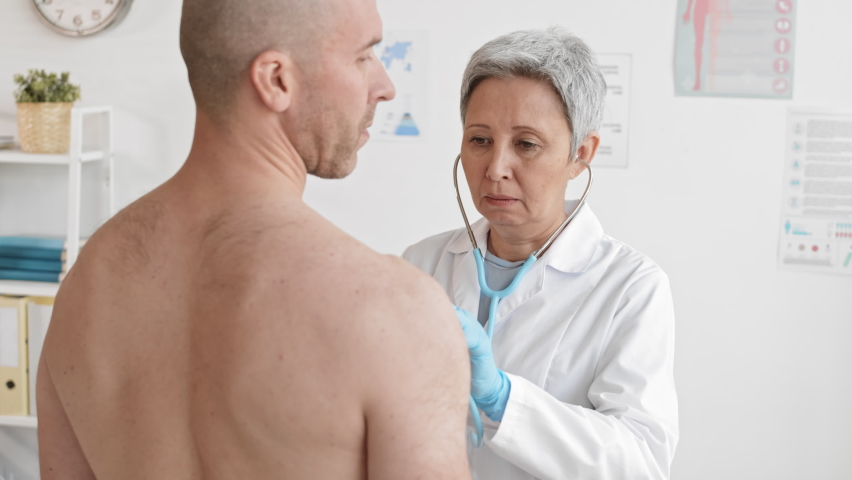 Medium over-the-shoulder of senior female doctor auscultating with stethoscope shirtless Caucasian adult male patient breathing in and out, standing in medical office | Shutterstock HD Video #1065982756