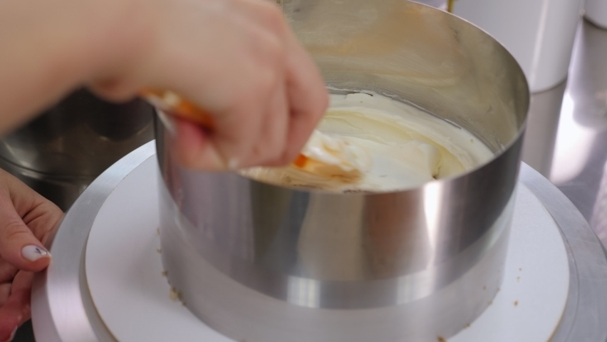 Close-up of the process of making a sweet delicious cake, the chef spreads white butter cream with a spatula on the biscuit cakes. | Shutterstock HD Video #1065982786