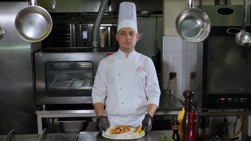 Close-up of the chef holding a dish of prawns in the kitchen of the restaurant, brings it to the camera offering it to you. | Shutterstock HD Video #1065982795