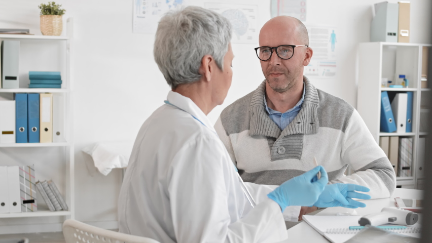 Over-the-shoulder slow motion of grey-haired unrecognizable female doctor checking throat with wooden tongue depressor of adult male Caucasian patient opening mouth widely, sitting in medical office | Shutterstock HD Video #1065983179