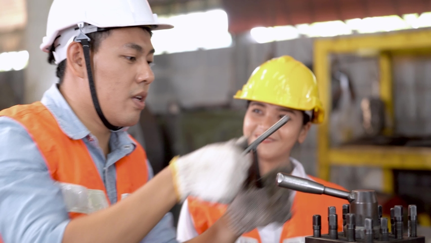 Asian workers factory man and woman working at heavy machine. Engineer inspect product and check equipment heavy machine. | Shutterstock HD Video #1065983299