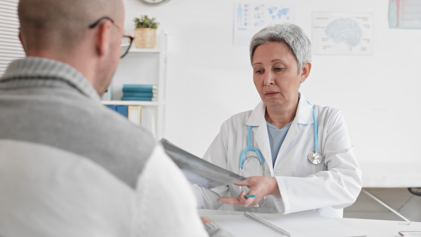 Over-the-shoulder slow motion of senior grey-haired Asian female doctor showing X-rays and talking to cropped adult patient sitting across desk at medical session | Shutterstock HD Video #1065983539
