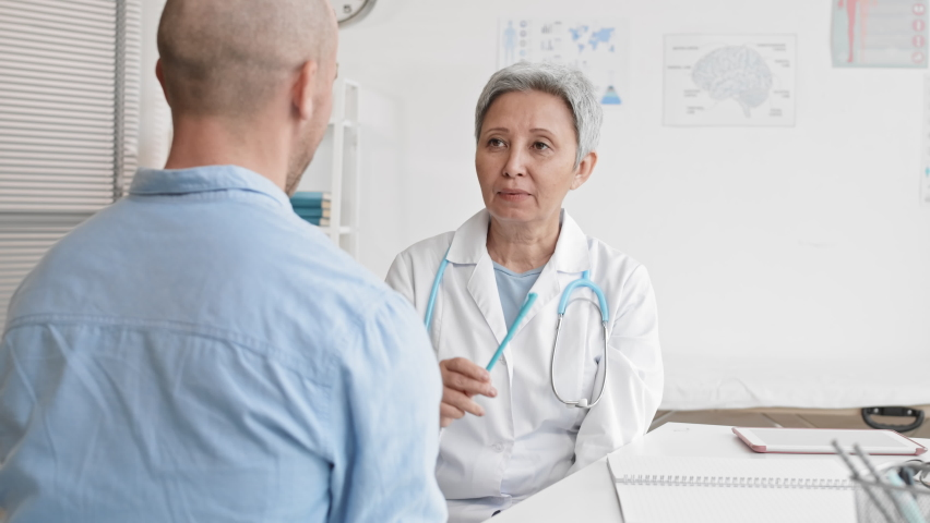 Medium over-the-shoulder of senior female Asian doctor sitting in medical office holding pen in hand and moving in front of unrecognizable male patient for oculomotor system checking | Shutterstock HD Video #1065983704