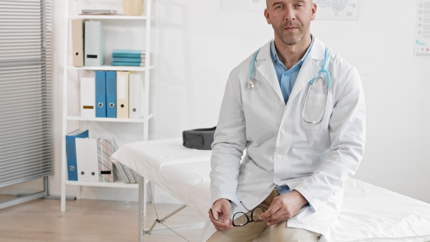 Medium POV of middle-aged Caucasian male doctor with stethoscope around neck sitting on examination couch in medical office, putting glasses on, talking and looking on camera | Shutterstock HD Video #1065983755
