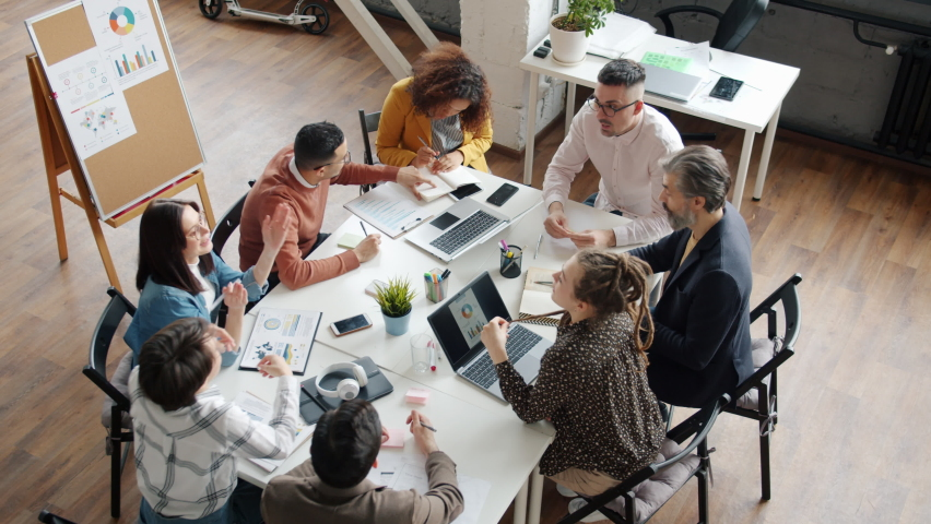 Office workers creative team are talking then doing high-five hand gesture working together around table. People and brainstorming activities concept. Royalty-Free Stock Footage #1066023490