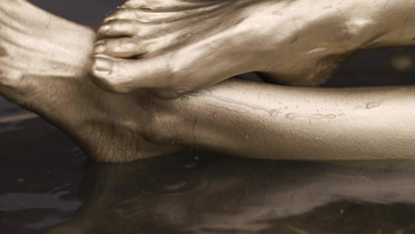 Naked feet of a female model with gold-colored skin is in the water in the water, posing. | Shutterstock HD Video #1066025122