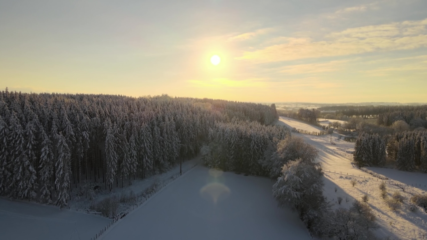 Sunny snow hill in the belgium eifel ,  ardennes. Snow landscape aerial drone view sunset Royalty-Free Stock Footage #1066030828