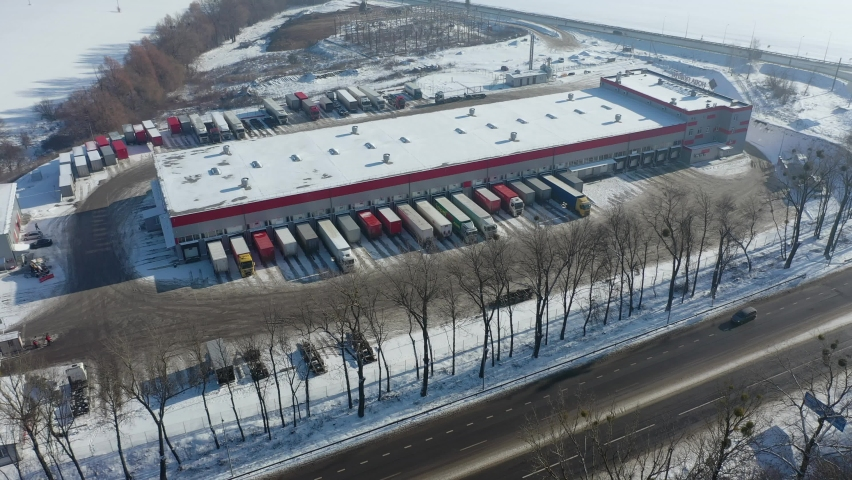 Aerial view of goods warehouse. Logistics center in industrial city zone from above. Aerial view of trucks loading at logistic center. View from drone. | Shutterstock HD Video #1066031659