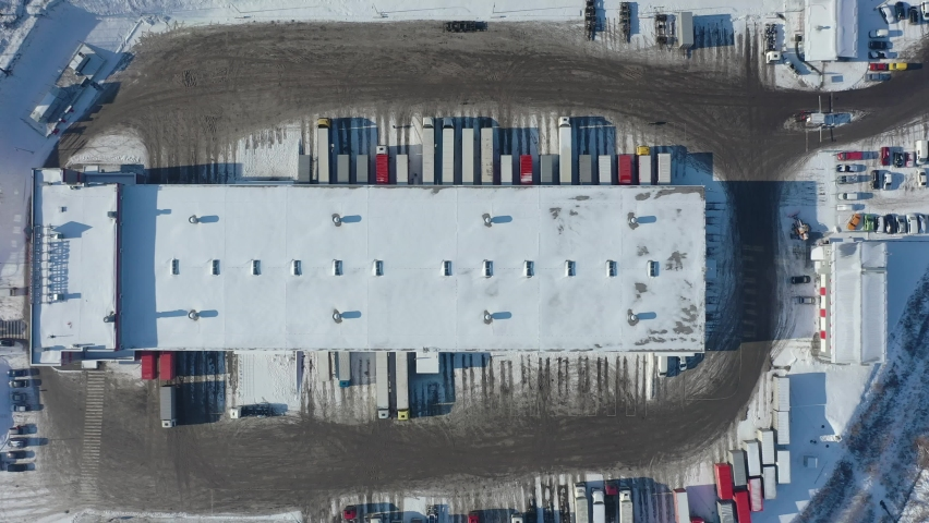 Aerial view of goods warehouse. Logistics center in industrial city zone from above. Aerial view of trucks loading at logistic center. View from drone. | Shutterstock HD Video #1066031662