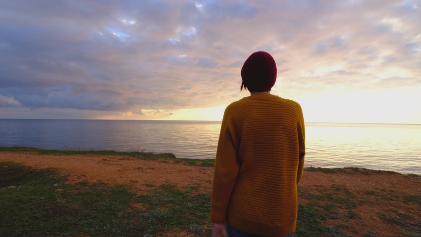Young Good-Looking Woman Wearing red hat and yellow sweater and Slowly Approaching Ocean. | Shutterstock HD Video #1066031983