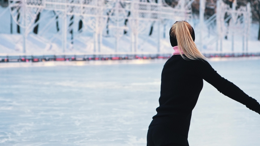 Young woman training her figure skating on public ice rink and looking in the camera | Shutterstock HD Video #1066032481