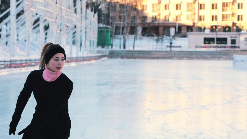 Young woman training her figure skating on public ice rink outdoors | Shutterstock HD Video #1066032484