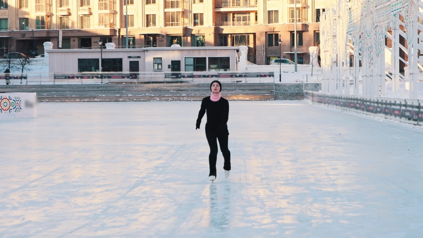Young beautiful woman skating on public ice rink - looking in the camera | Shutterstock HD Video #1066032490