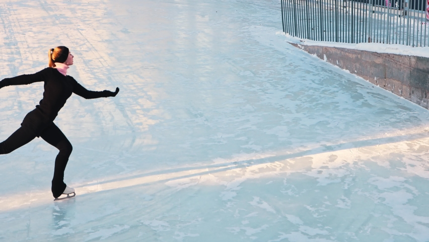 Young woman training her figure skating on public ice rink outdoors | Shutterstock HD Video #1066032496