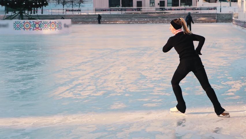 Young woman training her figure skating on public ice rink | Shutterstock HD Video #1066032499