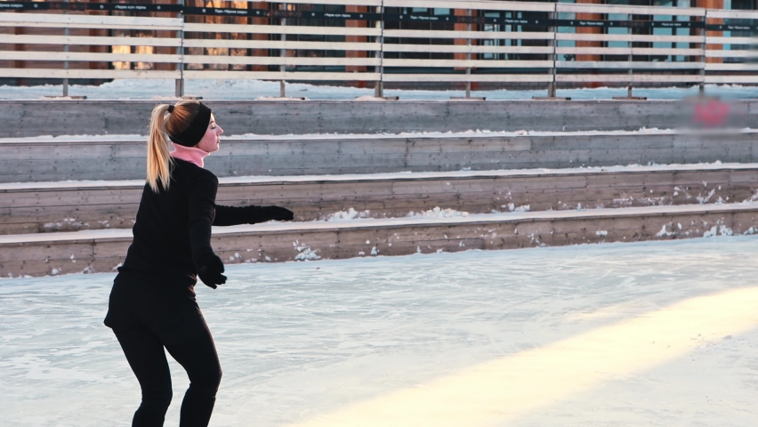 Young woman skating on public ice rink | Shutterstock HD Video #1066032511