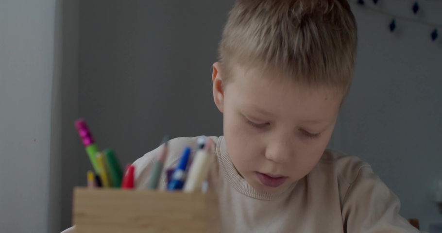 Close up portrait of blonde boy drawing at home sitting at table by window natural light. Serious kid child doing homework picture indoors slow motion. Art tools pen pencil equipment. Homeschooling | Shutterstock HD Video #1066032748
